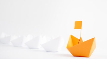 Leadership concept with orange paper ship leading among white