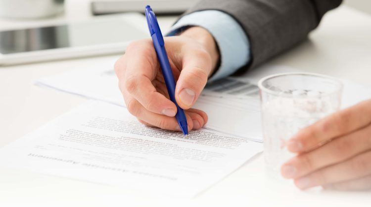 4 cs of insurance purchasing hands writing on paper while holding glass